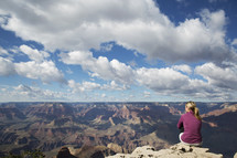 woman sitting at the edge of a canyon cliff
