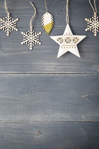 Snowflake and star ornaments on a wooden background.