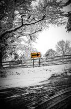 street sign and fence with snow