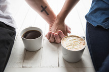 a couple holding hands and hot cocoa
