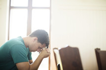 Man with hands clasped and head bowed,praying in a church pew.