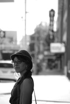 woman with a hat and purse standing on a sidewalk