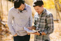 men standing outdoors reading a Bible on a fall day