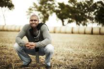 Man kneeling in field