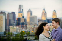 couple embracing - city skyline  background