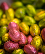 Chocolate Easter eggs covered in pink and yellow foil paper.