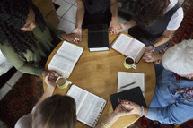 woman's group Bible study having a discussion and prayer around a table