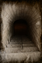 Dirty brick tunnel and stairway leading down into darkness.