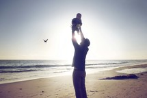 a father lifting up a baby on a beach