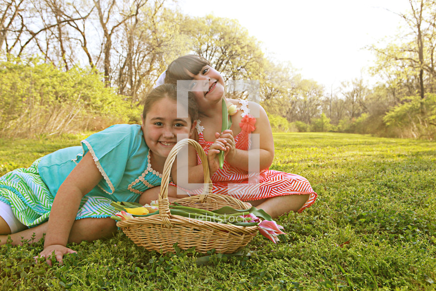Girl sitting in a field with basket