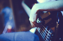 hand strumming the strings of an electric guitar