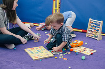 a toddler boy building puzzles in childcare