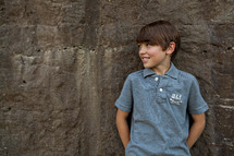 little boy standing in front of a concrete wall