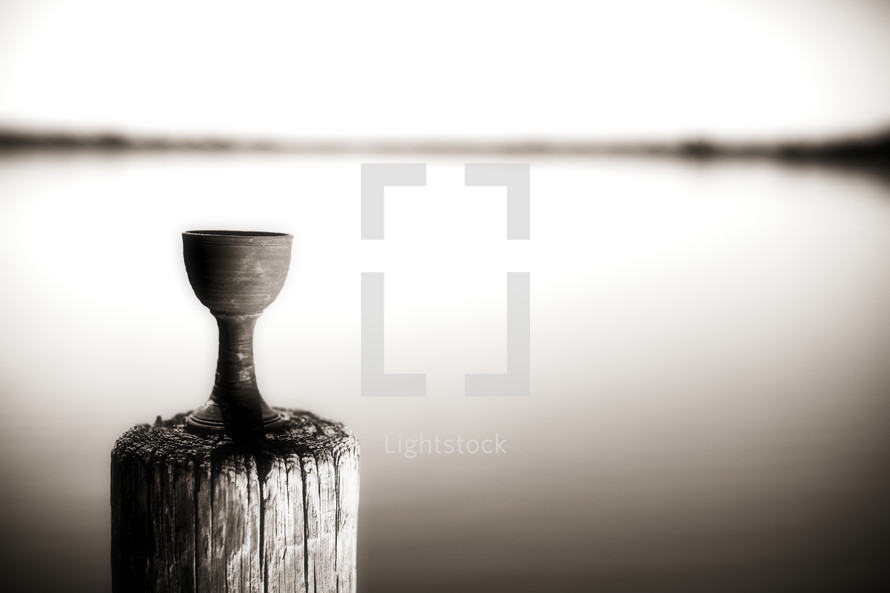 With the view of a lake in the background, a chalice sits on a dock.