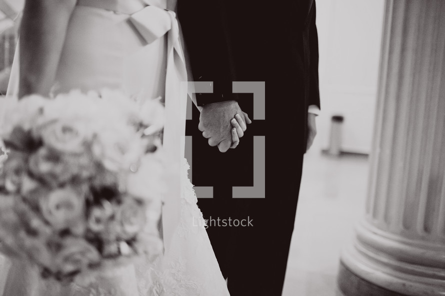 A bride and groom stand with hands held