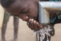 child drinking fresh water from a pipe of a new irrigation system