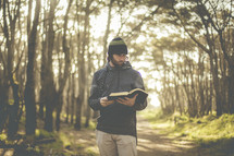 a man reading a Bible in a forest