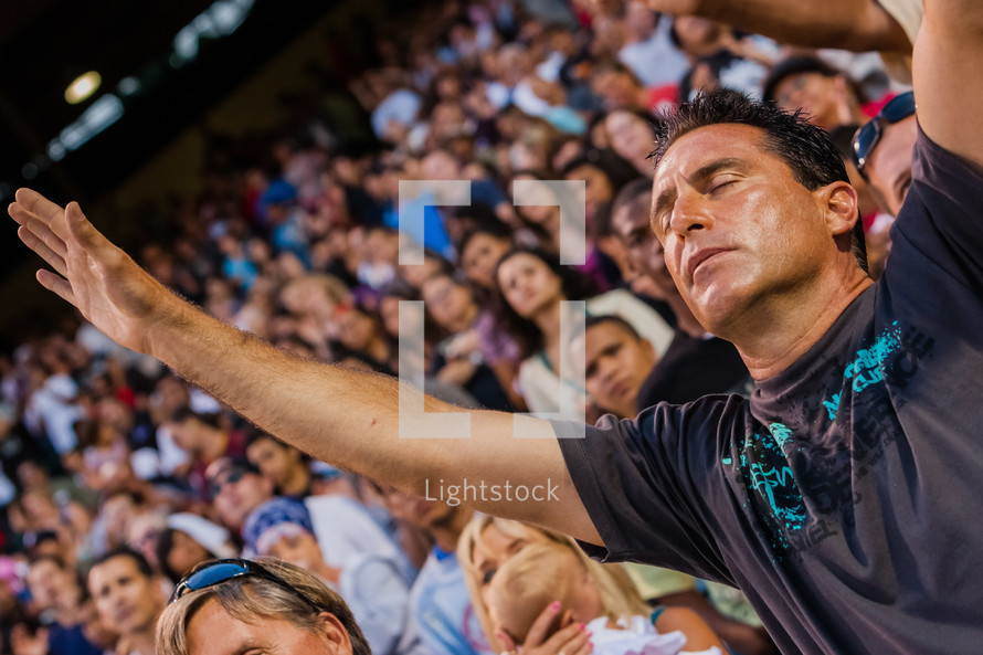 Man with eyes closed and face towards the sky with both arms raised in audience of people during worship service.
