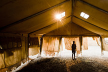 A boy standing alone in a tent