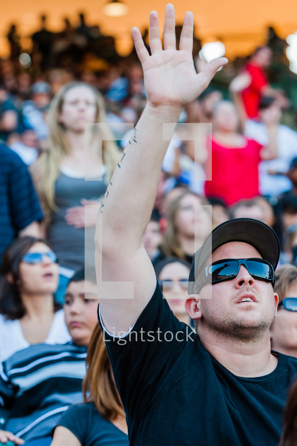 Man in sunglasses and baseball cap with right hand raised while looking to sky praise and worship