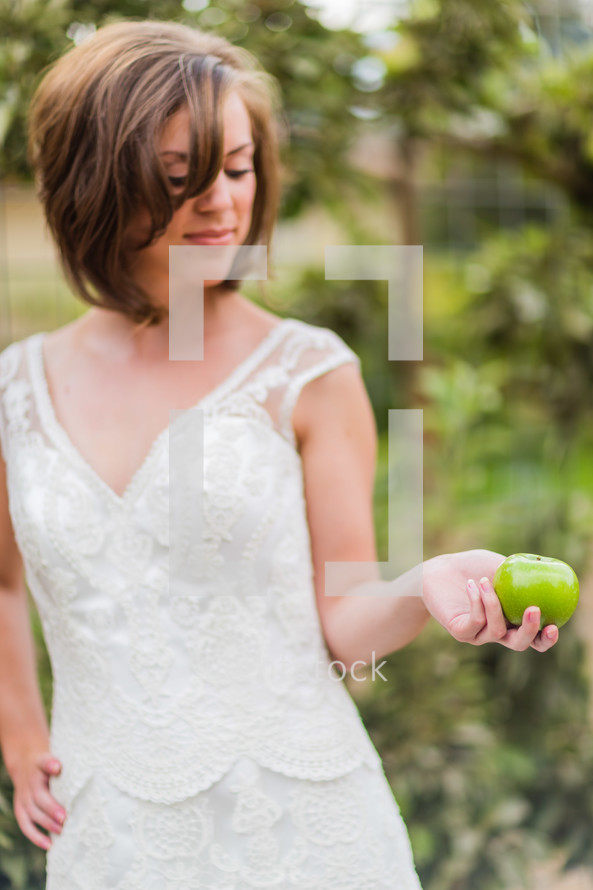 young woman girl in white dress holding a green apple
