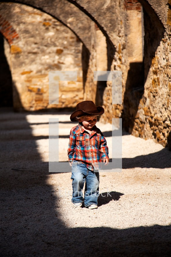 toddler in a cowboy hat walking on an arched covered walkway