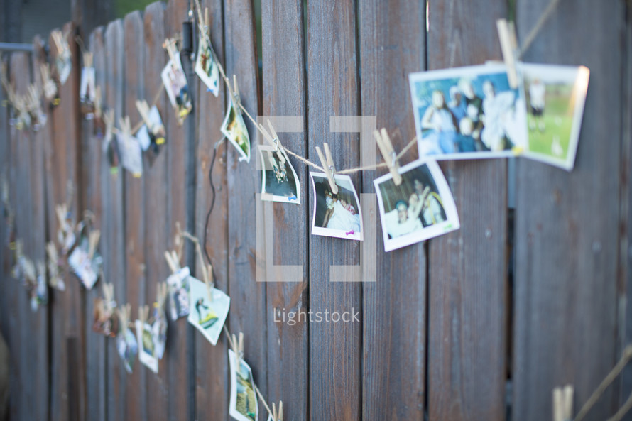 photos hanging on a line against a fence