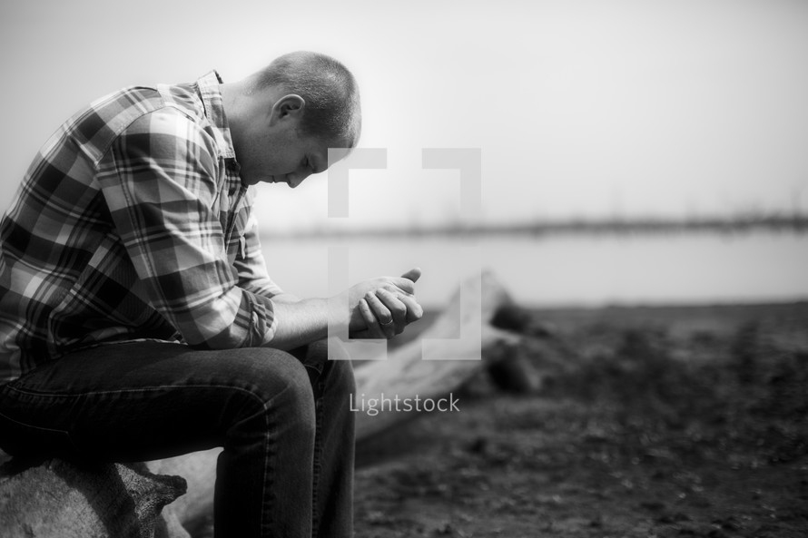 A man in a plaid shirt sitting on a log and praying.
