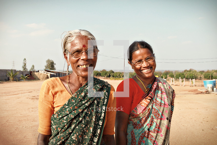 women smiling on a dirt road in India