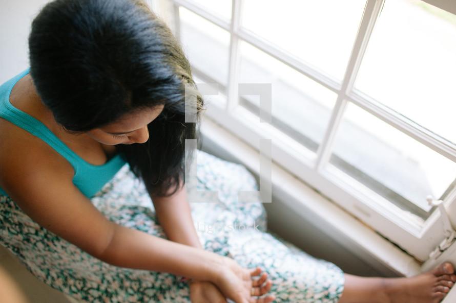 Female sitting near window