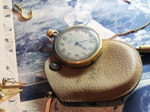 An antique pocket watch made out of brass sits on top of a Victorian piece of artwork and a leather pouch signifying time, productivity, creativity and hours worked on a project. Time is something we are always a slave to and seem to be running to keep up with but there is a God whom even time itself answers to and can stop the clock to give you a fresh outlook on life, longer years and longer life and the time to enjoy it. He holds the keys to all things - time, space and eternity.