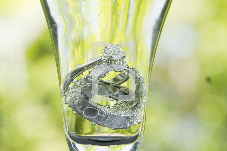 Wedding rings inside glass of water