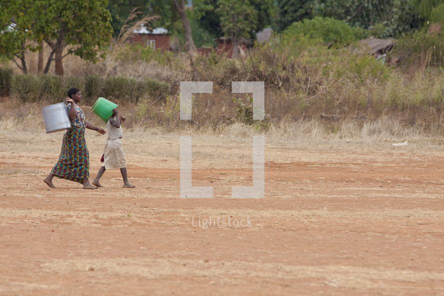 women carrying buckets down a dirt road