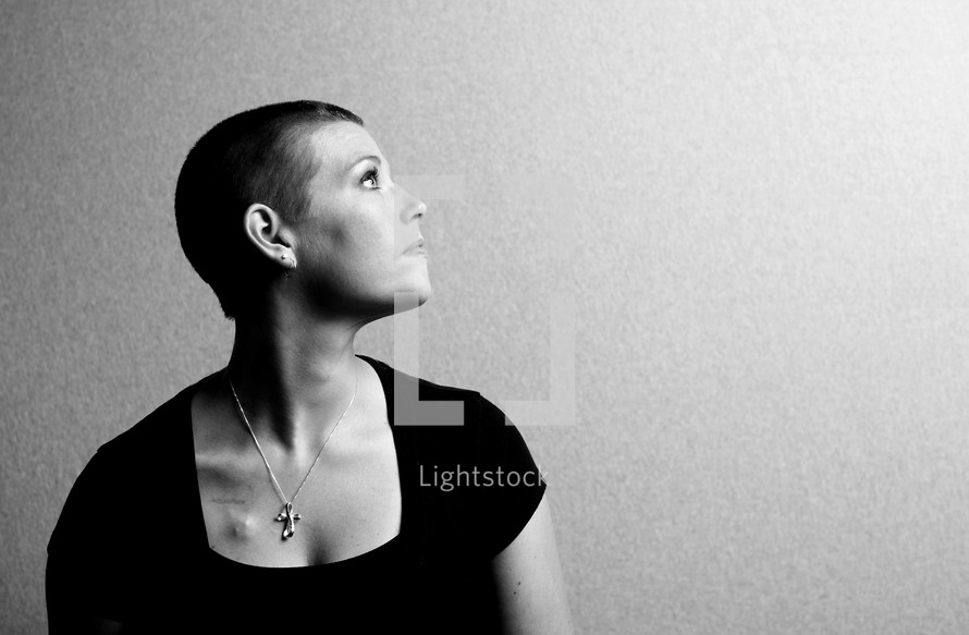 profile of a woman with shaved head wearing a cross necklace