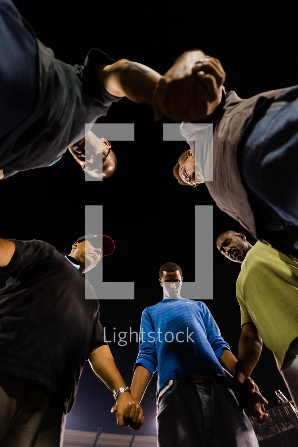 Men in prayer holding hands in a circle heads bowed