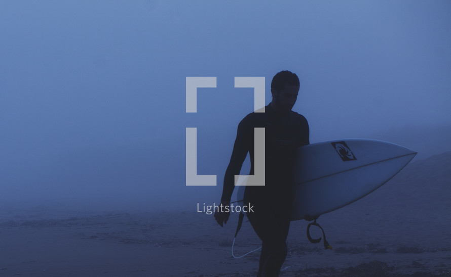 surfer walking on the beach holding a surf board