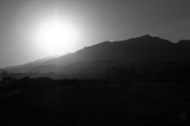 The sun setting behind a mountain.