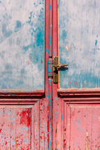 door latch on a red door with peeling paint
