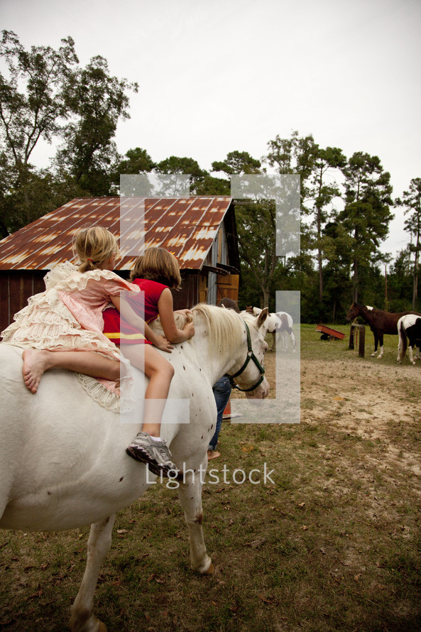 two kids riding a horse bare back