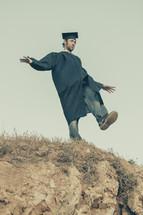 graduate balancing on a hill