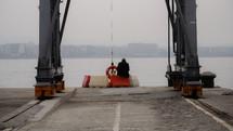 man sitting on a blockade on a dock