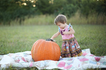 toddler girl on a blanket in the with a pumpkin