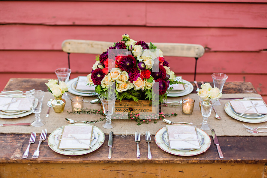 An outside table setting wedding country rustic chic plates forks spoons candles florals