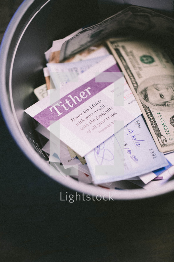 envelopes and cash in a bucket for offering
