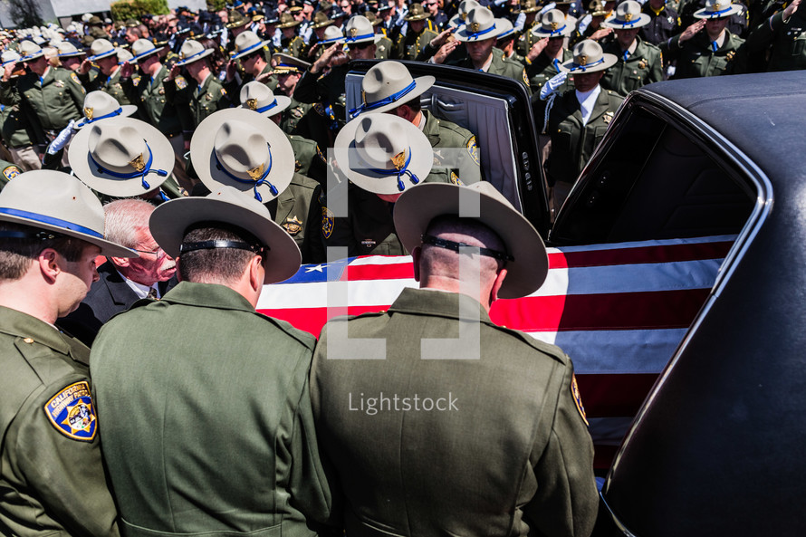 police officers putting a coffin into a hearse respect, honor highway patrol american flag casket salute