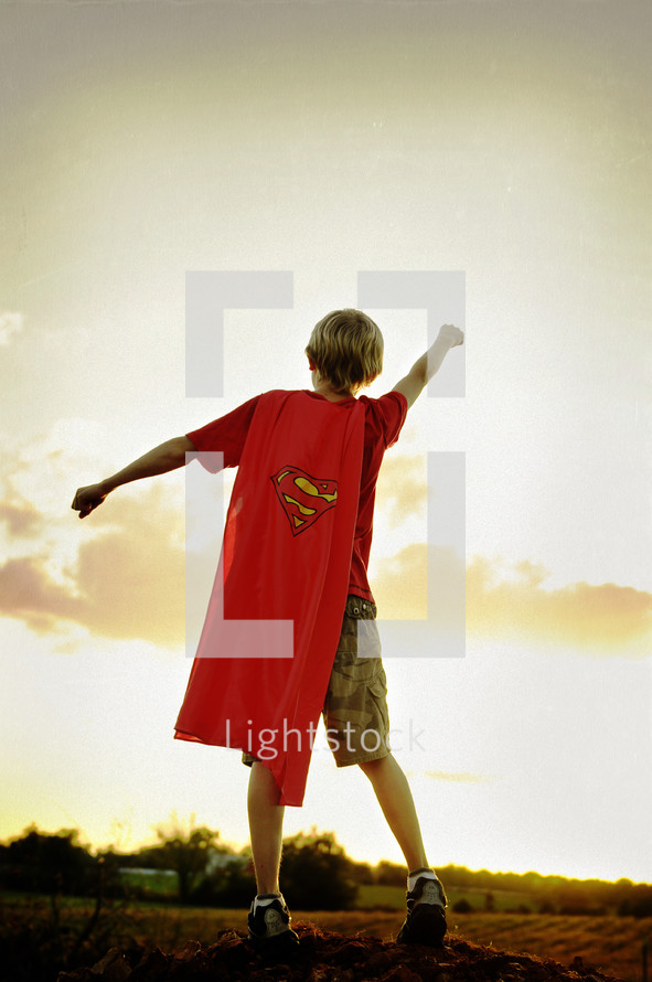 A boy in a superman cape with arms outstretched.