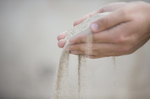Hands sifting sand