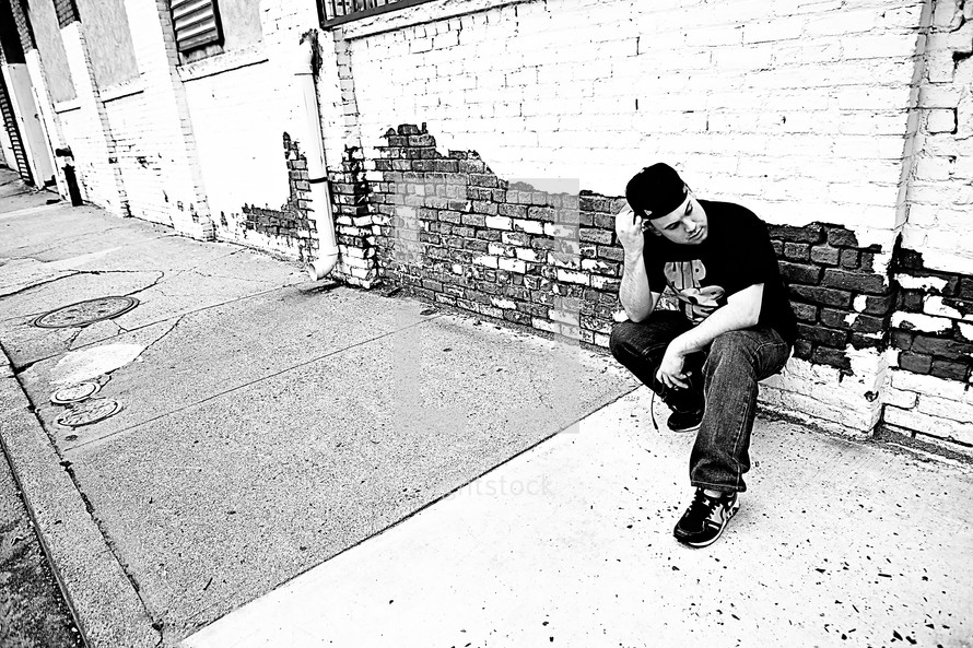 man crouched on a sidewalk in front of a brick wall