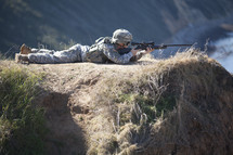 Soldier on hill aiming gun