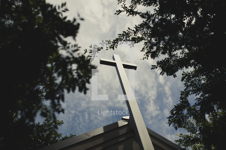 A cross positioned  on top of a church.